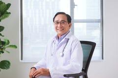 Portrait de docteur supérieur se reposant à son bureau dans le bureau médical Image stock