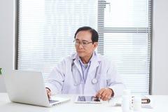 Portrait de docteur supérieur se reposant à son bureau dans le bureau médical Photo stock