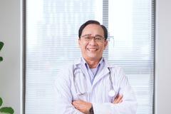 Portrait de docteur supérieur se tenant dans le bureau médical Image stock