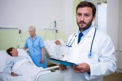 Portrait de docteur vérifiant un rapport médical Photographie stock