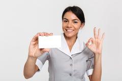 Portrait de domestique heureuse dans l'uniforme montrant la carte vide et l'OK de signe image libre de droits