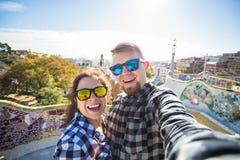Portrait de fabrication heureux de selfie de couples de voyage avec le smartphone en parc Guell, Barcelone, Espagne Beaux jeunes  Images libres de droits