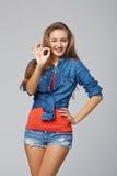 Portrait de faire des gestes correct femelle, sur le fond gris Photographie stock libre de droits