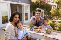 Portrait de famille à la maison mangeant le repas extérieur dans le jardin images libres de droits