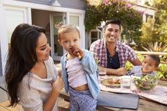 Portrait de famille à la maison mangeant le repas extérieur dans le jardin photos libres de droits