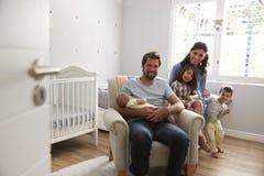Portrait de famille avec les enfants et le fils nouveau-né dans la crèche Photos stock