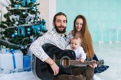 Portrait de famille avec une guitare pour Noël Photographie stock libre de droits