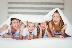 Portrait de famille couvert de couette sur le lit images stock