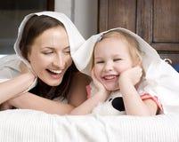 Portrait de famille, de mère et de fille heureuses dans le lit Image stock