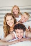 Portrait de famille de sourire sur le lit à la maison Images libres de droits