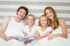 Portrait de famille de sourire sur le lit Image libre de droits