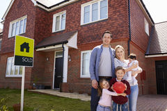 Portrait de famille en dehors de nouvelle maison avec le signe vendu image stock