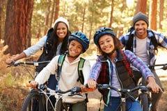 Portrait de famille faisant un cycle par la région boisée d'automne Image libre de droits