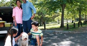 Portrait de famille heureuse à côté de leur voiture ayant l'amusement banque de vidéos