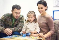 Portrait de famille heureuse avec la petite fille jouant le jeu de table Photographie stock