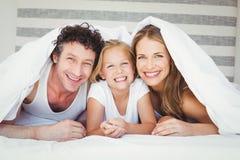 Portrait de famille heureuse couvert de couette Photos libres de droits