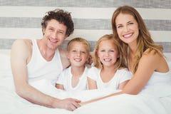 Portrait de famille heureuse détendant sur le lit Images libres de droits