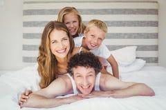 Portrait de famille heureuse de sourire sur le lit Photos stock