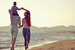 Portrait de famille heureuse et de bébé appréciant le coucher du soleil dans les loisirs d'été Images stock