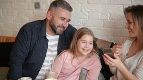 Portrait de famille heureuse faisant Selfie sur Smarthphone à l'intérieur Ils passent ce beau jour au café clips vidéos