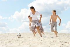 Portrait de famille heureuse jouant au football sur la plage dans le jour d'été photographie stock