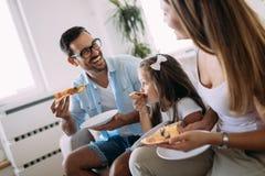 Portrait de famille heureuse partageant la pizza à la maison image stock