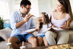 Portrait de famille heureuse partageant la pizza à la maison photographie stock