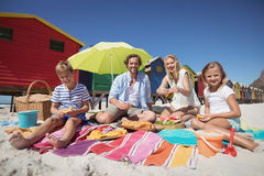 Portrait de famille heureuse se reposant ensemble sur la couverture à la plage Image libre de droits