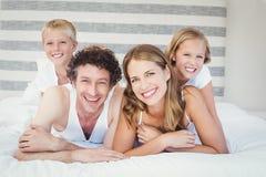 Portrait de famille heureuse se reposant sur le lit Image libre de droits