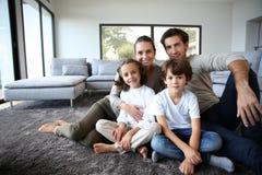 Portrait de famille heureuse se reposant sur le plancher images libres de droits