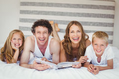 Portrait de famille heureuse tenant le livre sur le lit Images stock