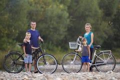 Portrait de famille de la jeune mère heureuse, le père et deux enfants blonds mignons, le garçon et la fille se tenant aux bicycl photo libre de droits