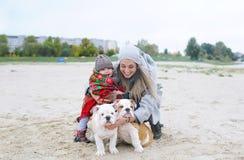 Portrait de famille de mère avec la petite fille et deux chiots d'un bouledogue en automne dehors Images stock