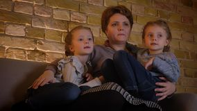 Portrait de famille de mère caucasienne avec deux filles s'étreignant et communiquant en atmosphère à la maison confortable banque de vidéos