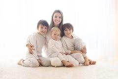Portrait de famille de mère et de ses trois garçons, d'isolement sur blanc, lumière de dos photographie stock libre de droits