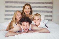 Portrait de famille se reposant sur le lit Image stock