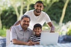 Portrait de famille sur plusieurs générations heureuse utilisant l'ordinateur portable au porche Image stock