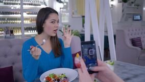 Portrait de femelle végétarienne avec la nourriture utile photographiée sur le smartphone pour les réseaux sociaux pendant le dîn banque de vidéos