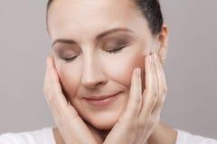 Portrait de femme âgée moyenne satisfaisante avec la relaxation parfaite de peau de visage après procédure de station thermale av image libre de droits