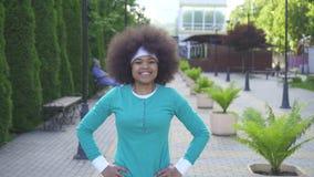 Portrait de femme africaine de sourire de sports avec une coiffure Afro en Sunny Park clips vidéos