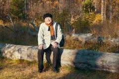 Portrait de femme agée aimable se reposant en parc d'automne Image stock