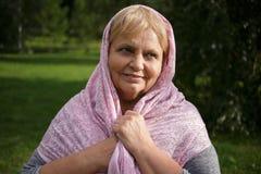 Portrait de femme assez supérieure dans l'écharpe sur le fond de nature Photo stock