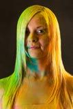 Portrait de femme attirante avec des couleurs vertes et jaunes Holi photographie stock libre de droits