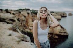Portrait de femme attirante posant sur la plage rocheuse avec le paysage de beauté photographie stock