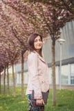 Portrait de femme au-dessus des arbres de floraison roses dehors Photo libre de droits