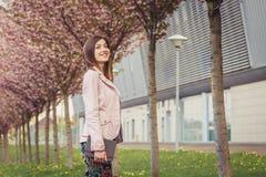 Portrait de femme au-dessus des arbres de floraison roses dehors Photos libres de droits