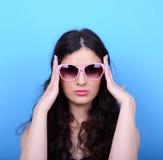 Portrait de femme avec de rétros verres sur le fond bleu Photographie stock libre de droits