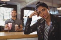 Portrait de femme avec l'ami tenant des verres de milkshake en café Photos stock