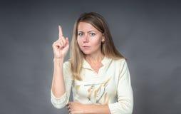 Portrait de femme avec le geste d'attention Elle tenant le doigt, avertissant écoutent moi pour faire attention Fermez-vous vers  photographie stock libre de droits