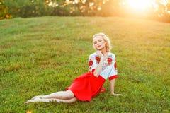 Portrait de femme blonde attirante avec le maquillage et la coiffure boucl?e dans la robe blanche rouge ?l?gante posant avec la t photographie stock